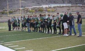 Courtesy photo The 2015 Eureka County High football team shakes hands with former coaches Grant Crutchley, Dennis Wells and Rod Garcia before the game against North Tahoe last Friday.