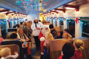 Santa Claus greets the train when it arrives at the North Pole and presents the children on board with a special gift.