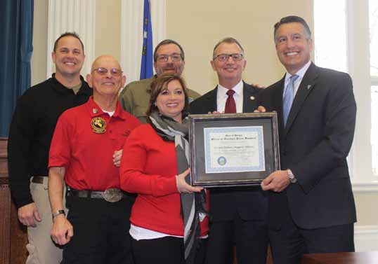 Steve Ranson  Teresa Di Loreto, center, executive director of the Nevada Military Support Alliance, accepts December's Veteran Supporter of the Month award from Gov. Brian Sandoval. From left are NMSA directors John Brownell, Dick Gammick, Jon Yuspa and Dan Morgan.